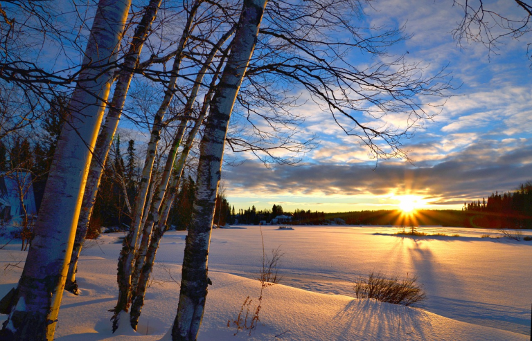 sunset over frozen lake, trees, clouds on blue sky
